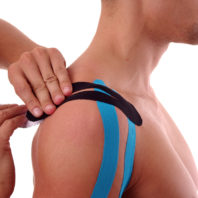 Kinesiology tape guide: How to tape shoder with kinesiology tape. shlder pain treatment. one man placing kinesiology tape on another man on white backgorund.
